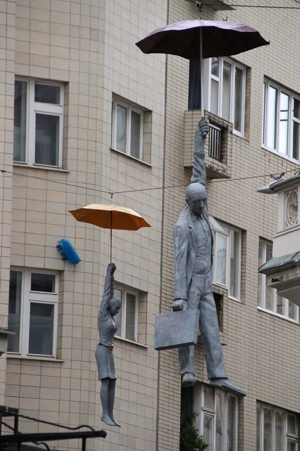 2 statues of people hanging from umbrellas