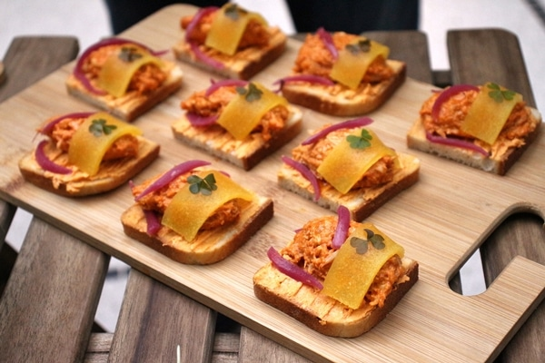 open faced chicken and peach sandwiches on a wooden board