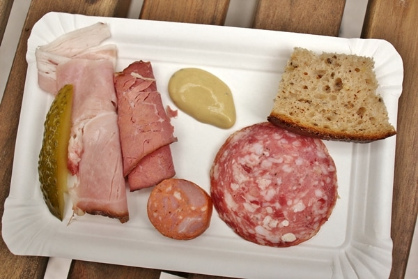 selection of ham and cured meats, bread, and mustard on a white plate