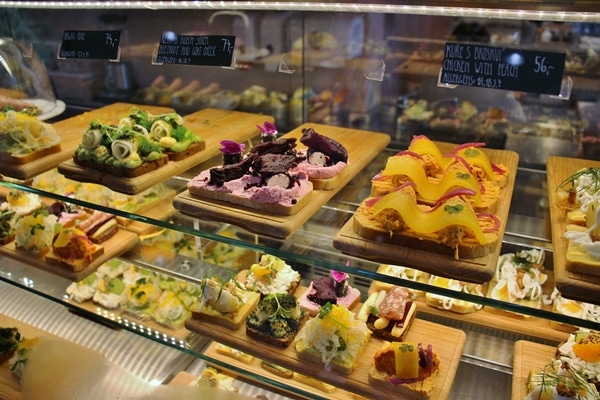 a variety of open-faced sandwiches in a display case