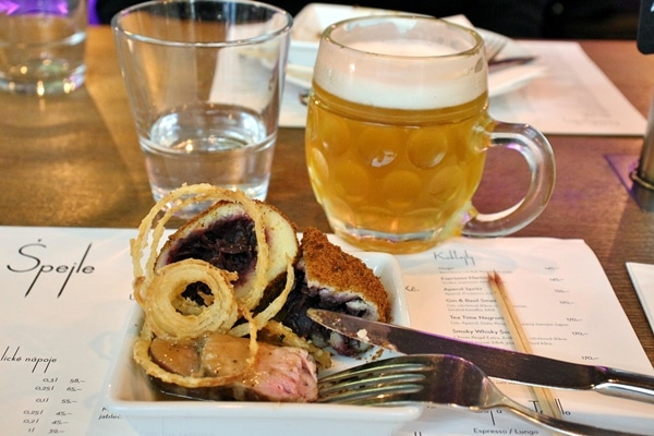 a plate of food and a mug of cold beer