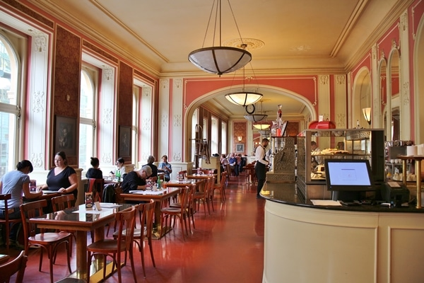 interior of the cafe section of Cafe Louvre in Prague with many tables and pink walls