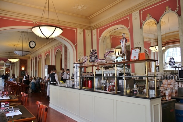 Cafe Louvre interior with pink wallpaper and coffee area