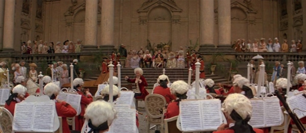 screenshot from the film Amadeus of Mozart conducting an orchestra