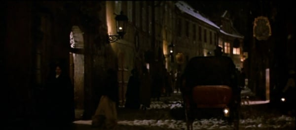 a screenshot from the movie Amadeus of a carriage going down a street at night