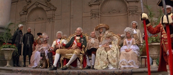 screenshot from the movie Amadeus of the emperor and others watching a concert outdoors