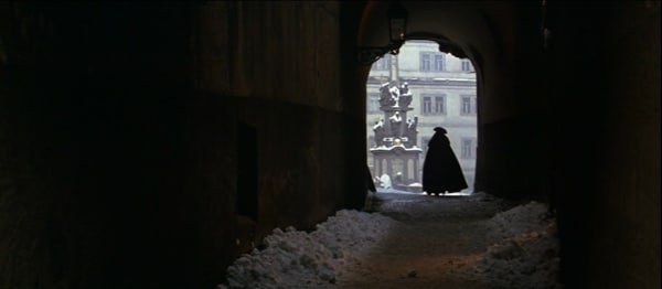 screenshot from the movie Amadeus of a cloaked man walking down a snowy tunnel
