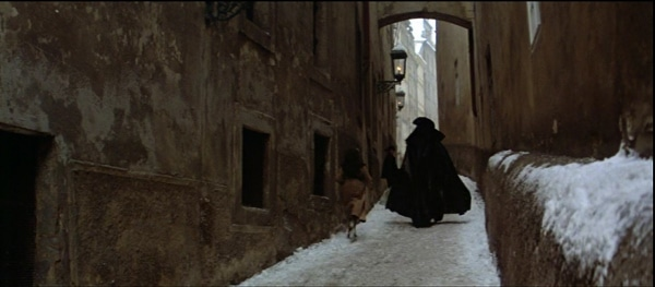 screenshot from the film Amadeus of a cloaked man walking down a narrow snowy street