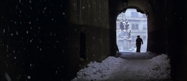 screenshot from the movie Amadeus of a man walking down a snowy tunnel