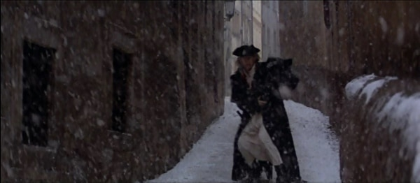screenshot from the film Amadeus of a man walking down a snowy narrow street