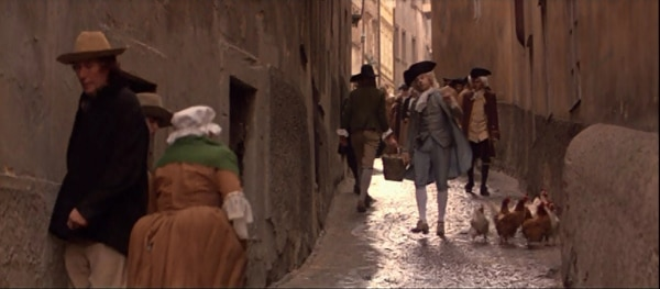 screenshot from the film Amadeus of Mozart walking down a cobblestone street