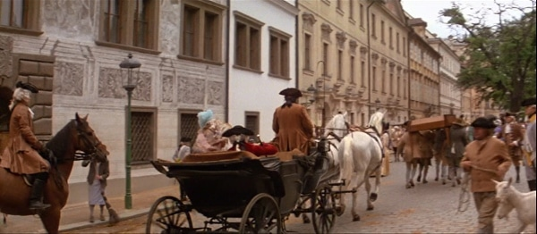 a screenshot from the movie Amadeus of a horse drawn carriage going down a street