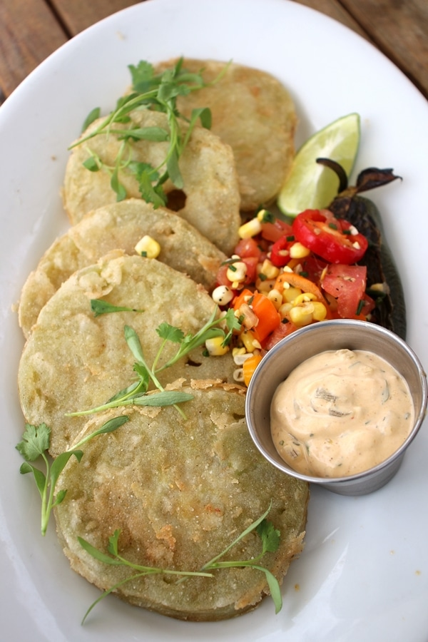 a plate of fried green tomatoes with corn salad and sauce