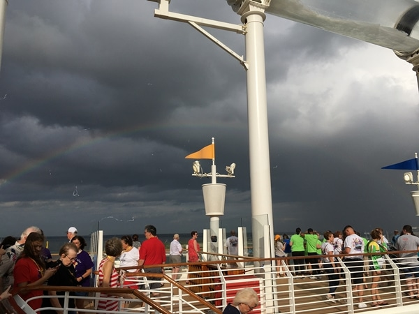 a rainbow in front of storm clouds as seen from cruise ship pool deck