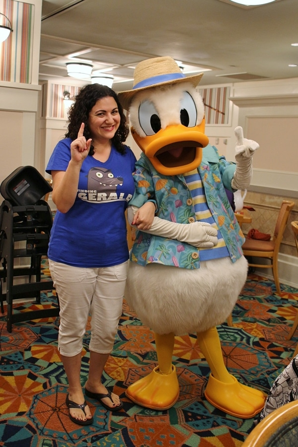 A woman posing with Donald Duck