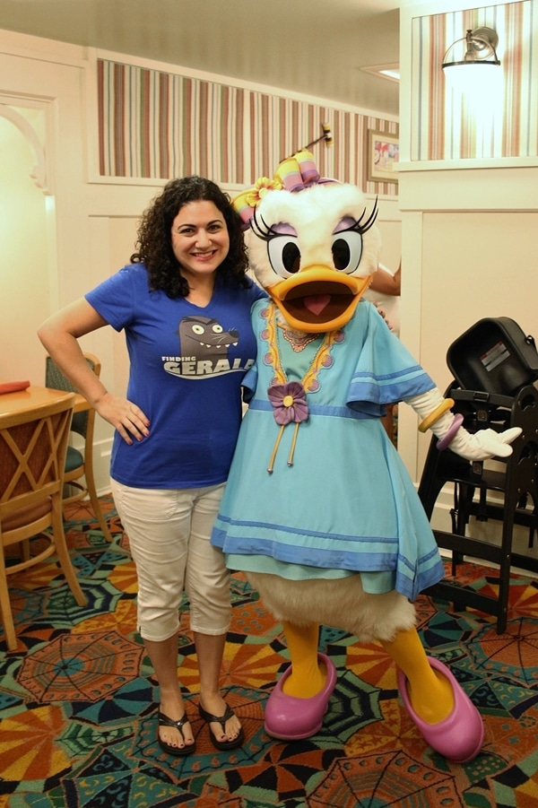 a woman posing with Daisy Duck
