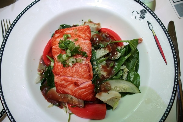 a salad topped with salmon filet