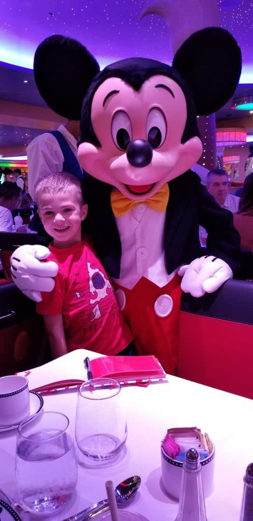 a boy posing with Mickey Mouse