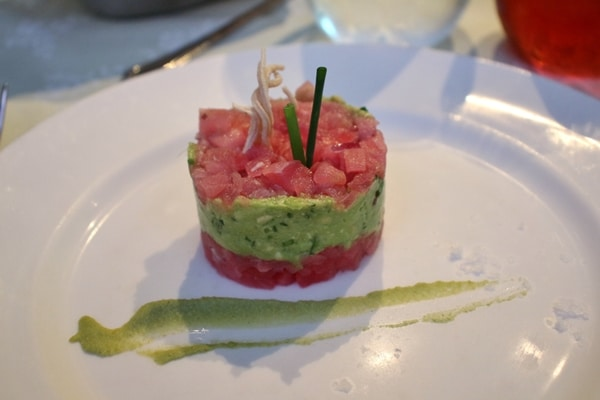 a raw tuna and avocado tower on a white plate
