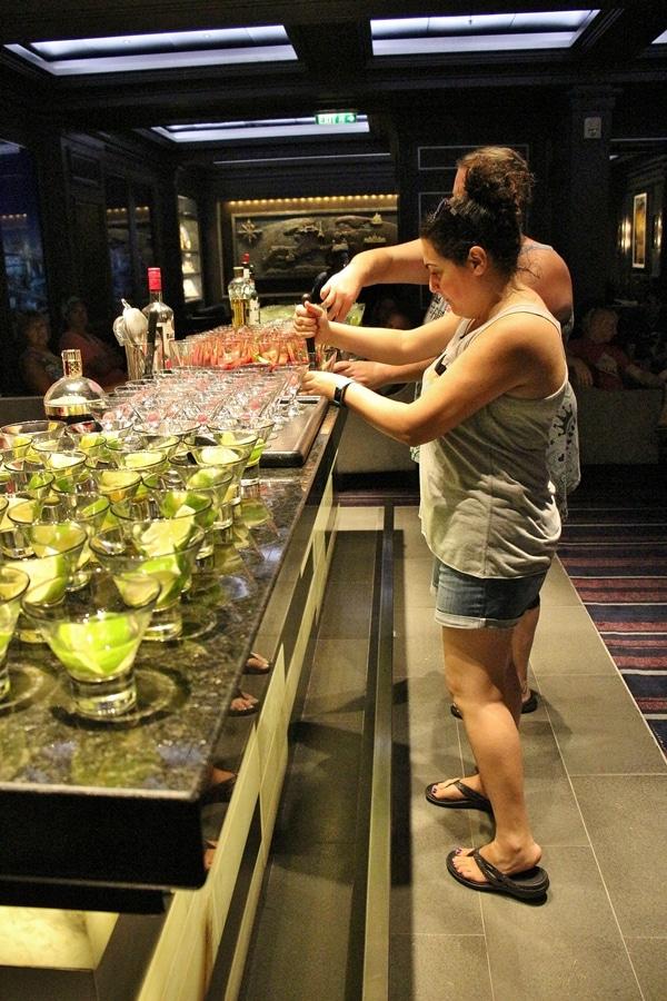 a woman making a cocktail at a bar