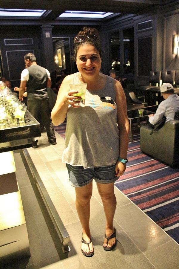 a woman holding up a mojito at a bar