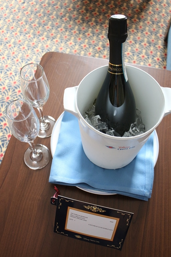 a bottle of Champagne in an ice bucket with glasses on the side