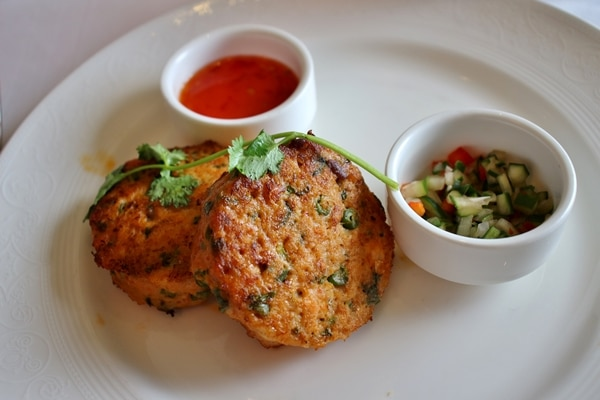 Thai fish cakes with red sauce on a white plate