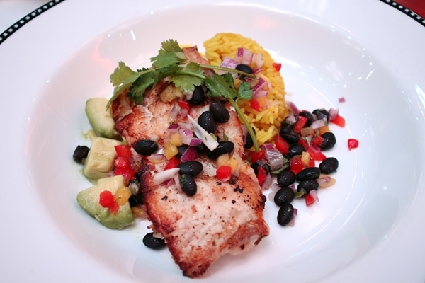 fish with black beans, vegetables, and rice on a plate