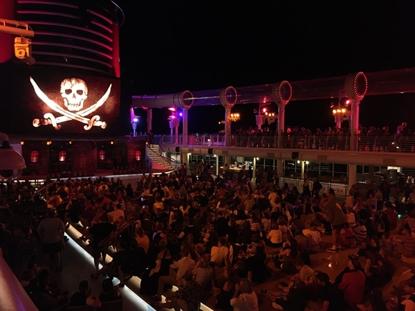 A group of people on the deck of a cruise ship at night