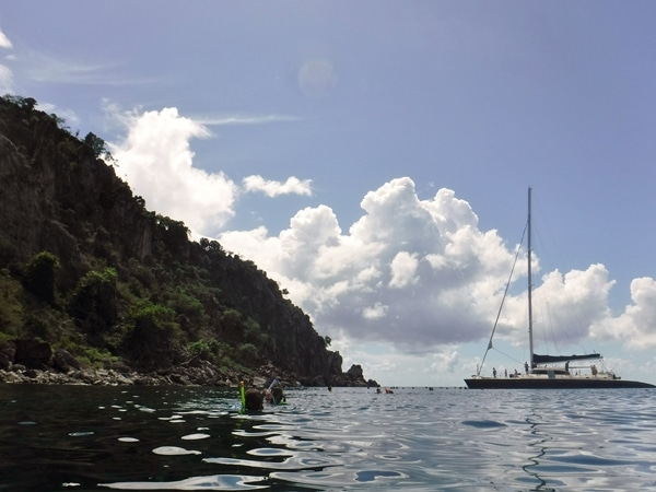 a catamaran in the distance with snorkelers in the water nearby