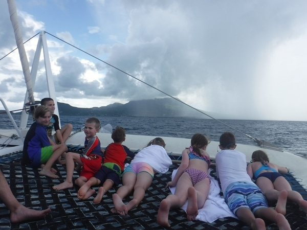 A group of people sitting in a catamaran looking at a storm in the distance