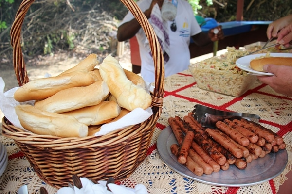 A basket of bread and platter of hot dogs