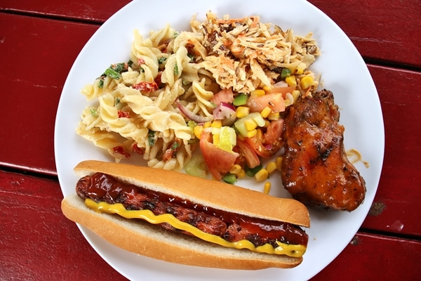 A plate of food with a hot dog and pasta salad