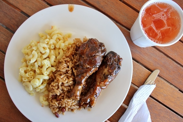 A plate of chicken, rice, and macaroni salad on a wooden table