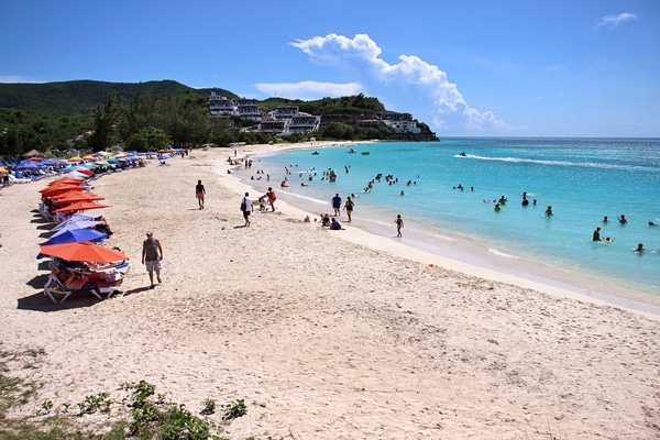 A group of people on a Caribbean beach with turquoise water
