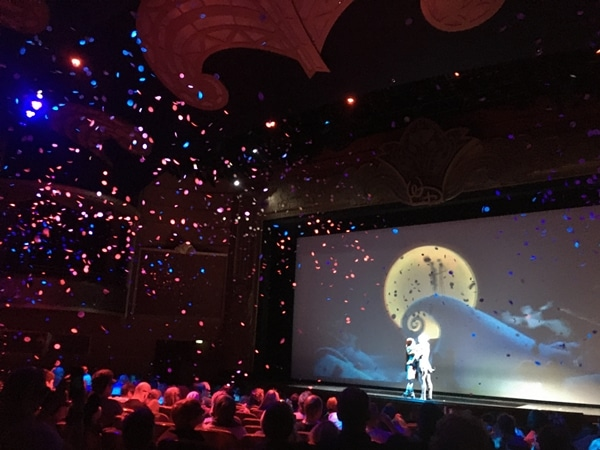a movie screening in a theater with confetti falling down