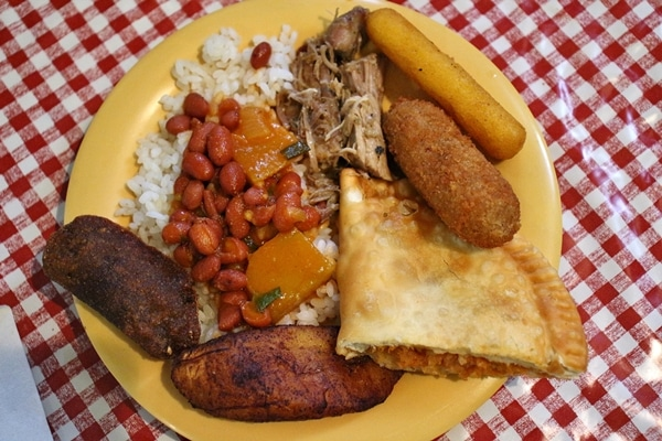 A plate of Puerto Rican food in a yellow plate on a checkered tablecloth
