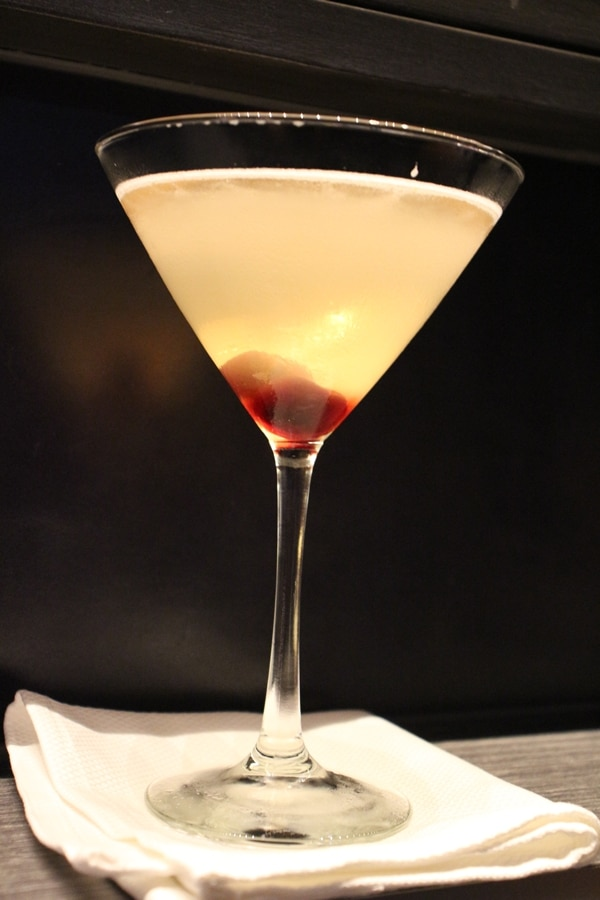 Cocktail glass with opaque white drink and cherry garnish