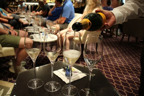 a server pouring Champagne into glasses