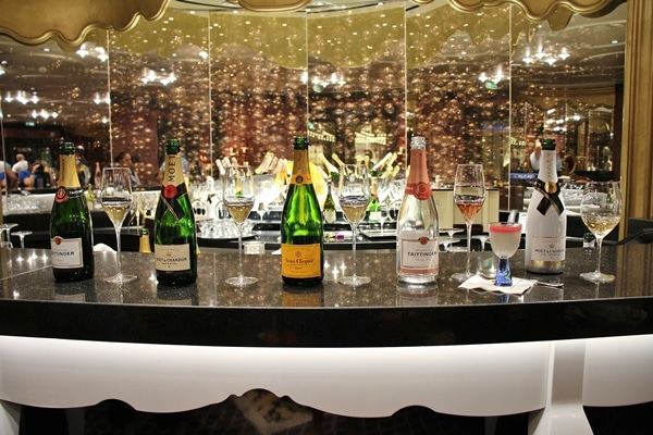 A row of Champagne bottles lined up in the Ooh La La lounge on the Disney Fantasy