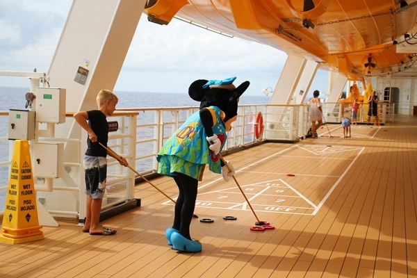 Minnie Mouse playing shuffleboard with a young boy on a cruise ship