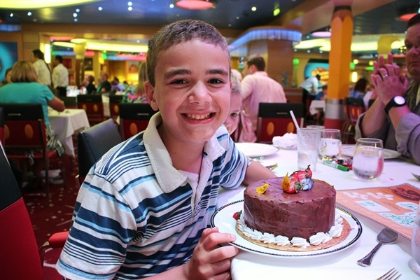 A person sitting at a table with a birthday cake