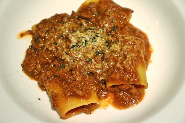 large tubular pasta with meat sauce and cheese on top