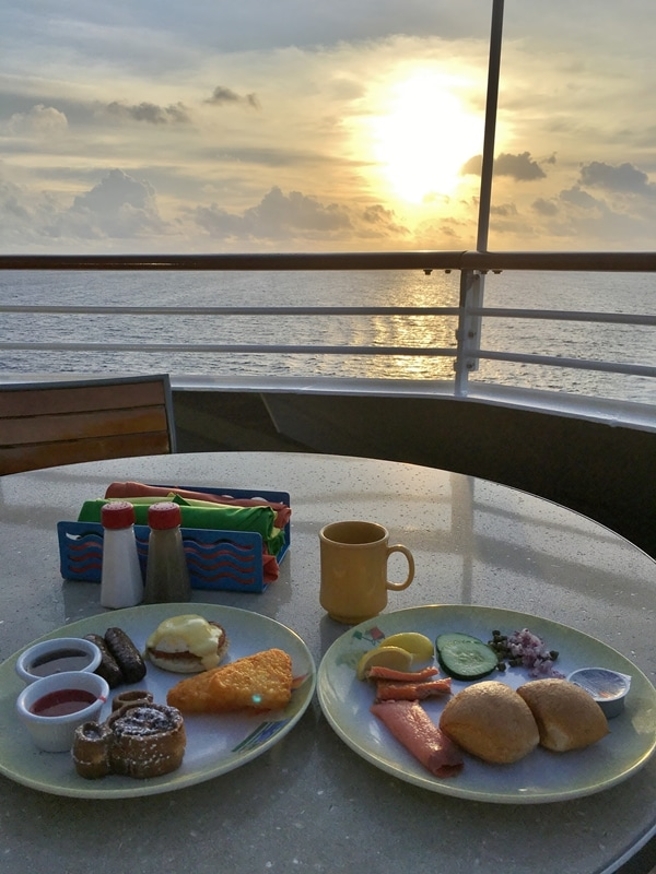 plates of food on a table overlooking the water on a cruise ship