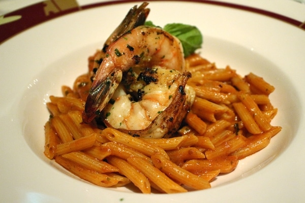 a bowl of penne pasta with tomato sauce, and grilled jumbo shrimp