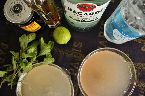 Overhead view of 2 cocktail glasses with drinks, and a variety of ingredients lined up