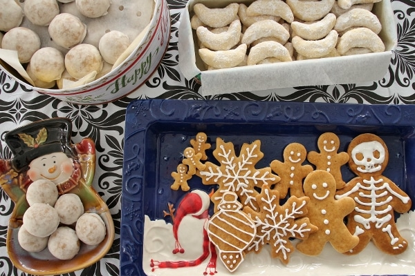 a variety of Christmas cookies served on plates and in cookie tins