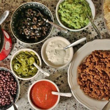 Nacho bar with bowls of various toppings