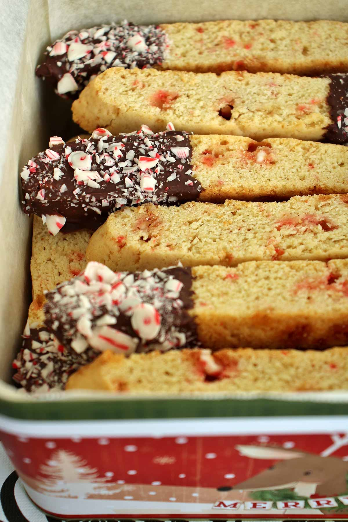 Closeup of a square cookie tin filled with chocolate and peppermint dipped biscotti cookies.