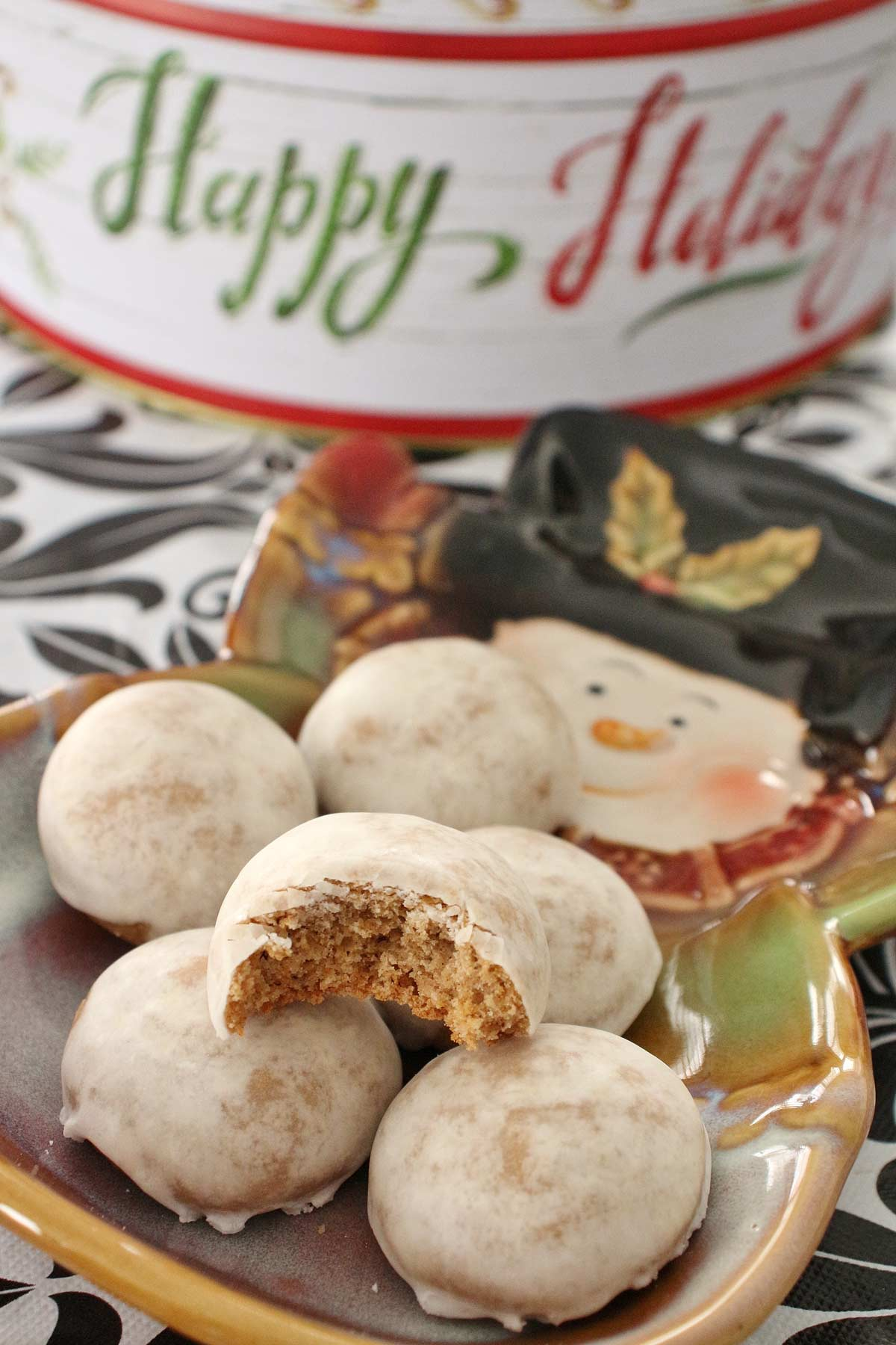 Round iced spice cookies piled on a snowman shaped plate.